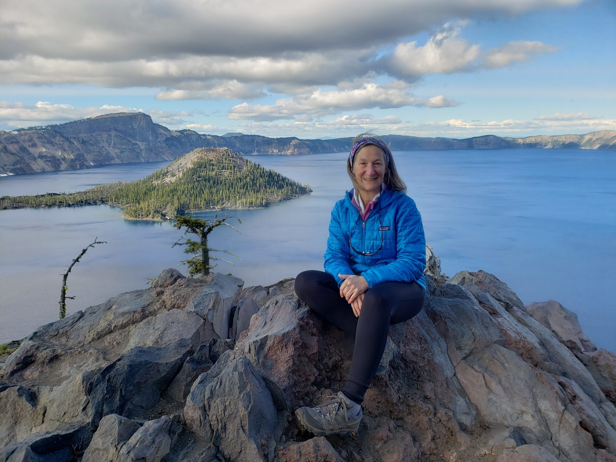 Debra Mailman sits atop a stone outcropping in front of a body of water.