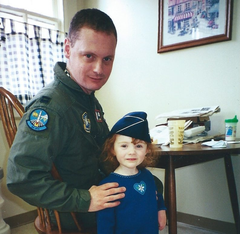 Photo of Lt. Col. Loftis with 2-year-old Alison wearing his Air Force cap