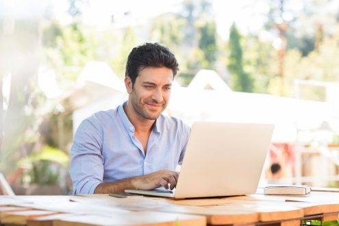 A man smiles and works on his laptop